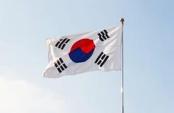 Bandera de la Corea del Sur que agita con el cielo azul en fondo Foto de archivo