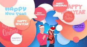 Bandera de la Feliz Año Nuevo con el hombre y la mujer en cartel de la Feliz Navidad de las burbujas de Santa Hats Over Abstract  Imagen de archivo libre de regalías