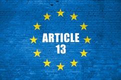 Bandera de la inscripción del artículo 13 y de unión europea en la pared de ladrillo azul fotos de archivo libres de regalías