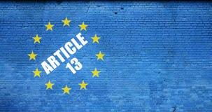 Bandera de la inscripción del artículo 13 y de unión europea en la pared de ladrillo azul foto de archivo libre de regalías
