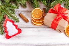 Bandera de la Navidad con el árbol verde, el giftbox, la decoración hecha a mano del fieltro, la naranja y el canela en el fondo  Fotos de archivo