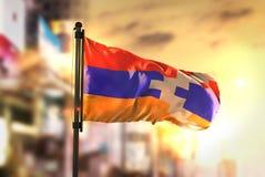 Bandera de la república de Nagorno Karabaj contra el fondo borroso ciudad A Fotos de archivo libres de regalías