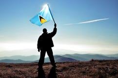 Bandera de la Santa Lucía de la silueta que agita del ganador acertado del hombre encima de la montaña imagen de archivo libre de regalías
