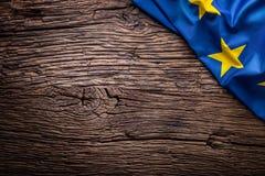 Bandera de la unión de Europa en viejo fondo de madera La UE señala el viejo fondo del roble por medio de una bandera vertical Fotos de archivo