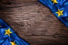 Bandera de la unión de Europa en viejo fondo de madera La UE señala el viejo fondo del roble por medio de una bandera vertical Imagen de archivo libre de regalías