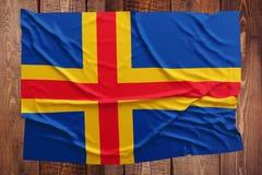 Bandera de las islas de Aland en un fondo de madera de la tabla Opini?n superior arrugada de la bandera fotos de archivo