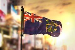 Bandera de las islas de Pitcairn contra fondo borroso ciudad en la salida del sol Imagenes de archivo