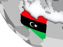 Bandera de Libia en el globo político Imagen de archivo libre de regalías
