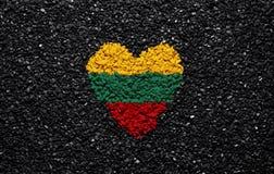 Bandera de Lituania, bandera lituana, corazón en el fondo negro, piedras, grava y tabla, papel pintado foto de archivo