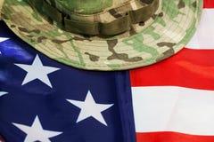 Bandera de los E.E.U.U. con el sombrero del combate del camuflaje Foto de archivo