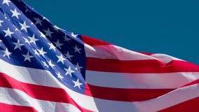 Bandera de los E.E.U.U. en el cielo azul metrajes