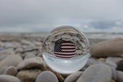 Bandera de los Estados Unidos de América pintada en una piedra después de una bola de cristal en la playa foto de archivo