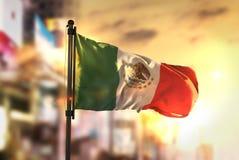 Bandera de México contra fondo borroso ciudad en el contraluz de la salida del sol imagen de archivo