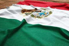 Bandera de M?xico en un fondo de madera del escritorio Opini?n superior de seda de la bandera mexicana fotos de archivo