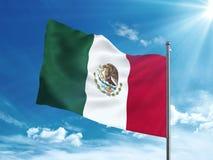 Bandera de México que agita en el cielo azul Fotos de archivo