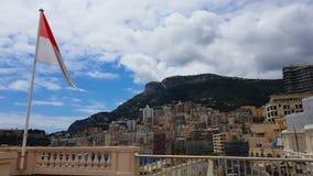 Bandera de Mónaco que agita contra el fondo del paisaje urbano de la montaña y del centro turístico metrajes