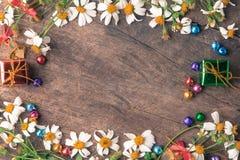 Bandera de madera del fondo de la Navidad y del Año Nuevo con con la caja de regalo, bolas del caramelo de la flor de la margarit Fotos de archivo libres de regalías