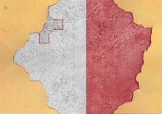 Bandera de Malta en fachada agrietada concreta material rota grande del agujero imagen de archivo