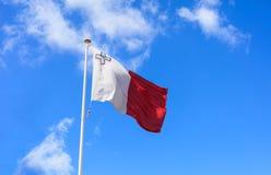 Bandera de Malta Bandera de Malta en un polo que agita en fondo del cielo azul imagen de archivo libre de regalías