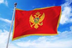 Bandera de Montenegro que se convierte contra un cielo azul imagen de archivo libre de regalías