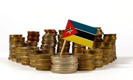 Bandera de Mozambique con la pila de monedas del dinero Fotografía de archivo