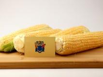 Bandera de New Jersey en un panel de madera con el maíz aislado en un blanco Imagen de archivo