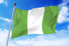 Bandera de Nigeria que se convierte contra un cielo azul foto de archivo libre de regalías