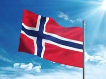 Bandera de Noruega que agita en el cielo azul Foto de archivo