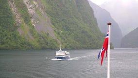Bandera de Noruega que agita en el fondo del fiordo Noruega almacen de metraje de vídeo