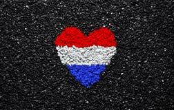 Bandera de Países Bajos, corazón en el fondo, las piedras, la grava y la tabla negros, papel pintado fotografía de archivo libre de regalías