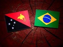 Bandera de Papúa Nueva Guinea con la bandera brasileña en un isolat del tocón de árbol imagenes de archivo