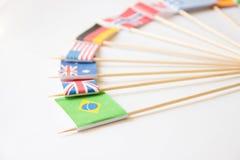 Bandera de papel brasileña entre otras banderas de países en blanco Fotos de archivo libres de regalías