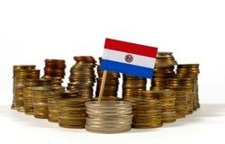 Bandera de Paraguay con la pila de monedas del dinero Imagen de archivo