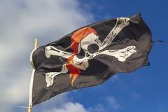Bandera de pirata 'Jolly Roger 'en un fondo del cielo azul con las nubes en un día soñoliento brillante fotografía de archivo libre de regalías