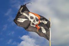 Bandera de pirata 'Jolly Roger 'en un fondo del cielo azul con las nubes en un día soñoliento brillante fotos de archivo libres de regalías