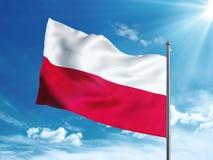 Bandera de Polonia que agita en el cielo azul Imágenes de archivo libres de regalías
