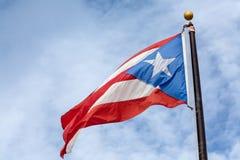 Bandera de Puerto Rico en fondo nublado Imagen de archivo libre de regalías