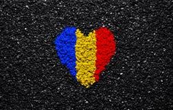 Bandera de Rumania, bandera rumana, corazón en el fondo negro, piedras, grava y tabla, papel pintado foto de archivo libre de regalías