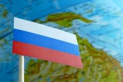 Bandera de Rusia con un mapa del globo como fondo Imágenes de archivo libres de regalías