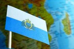 Bandera de San Marino con un mapa del globo como fondo Fotos de archivo
