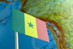 Bandera de Senegal con un mapa del globo como fondo Foto de archivo libre de regalías
