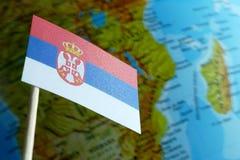 Bandera de Serbia con un mapa del globo como fondo Imagen de archivo libre de regalías