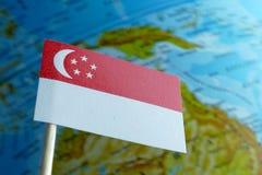 Bandera de Singapur con un mapa del globo como fondo Fotos de archivo libres de regalías