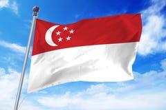 Bandera de Singapur que se convierte contra un cielo azul claro Imagen de archivo