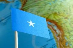 Bandera de Somalia con un mapa del globo como fondo Imágenes de archivo libres de regalías