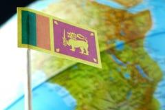 Bandera de Sri Lanka con un mapa del globo como fondo Imagen de archivo libre de regalías
