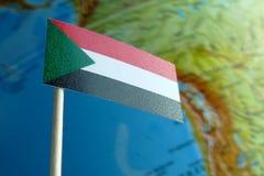 Bandera de Sudán con un mapa del globo como fondo Fotografía de archivo libre de regalías