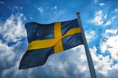 Bandera de Suecia con el cielo azul y las nubes en el fondo Fotografía de archivo
