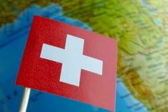 Bandera de Suiza con un mapa del globo como fondo Imagen de archivo libre de regalías