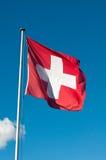 Bandera de Suiza contra el cielo azul Fotos de archivo libres de regalías